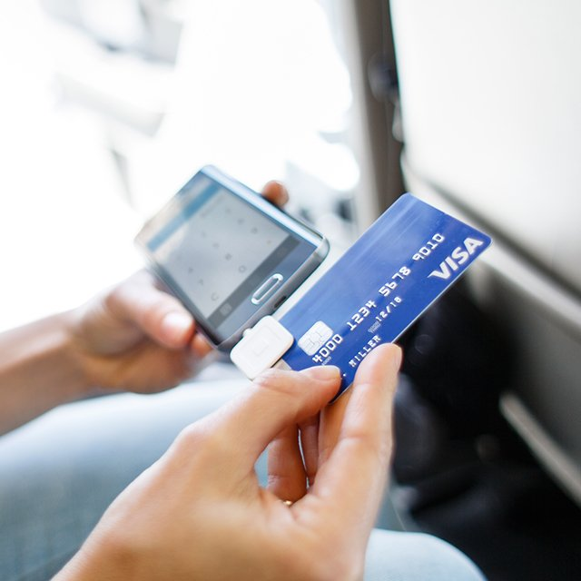 Woman swiping card in taxi