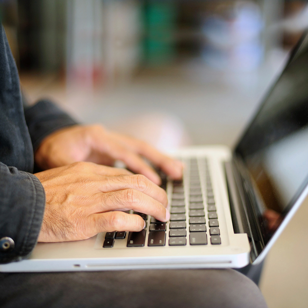 Close up of a man typing on a laptop.