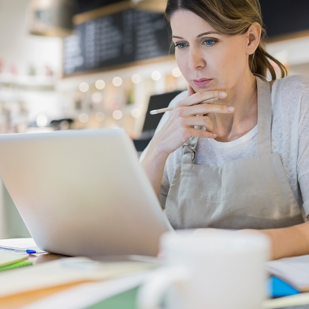 A woman sitting at a desk, looking pensive while staring at her laptop.