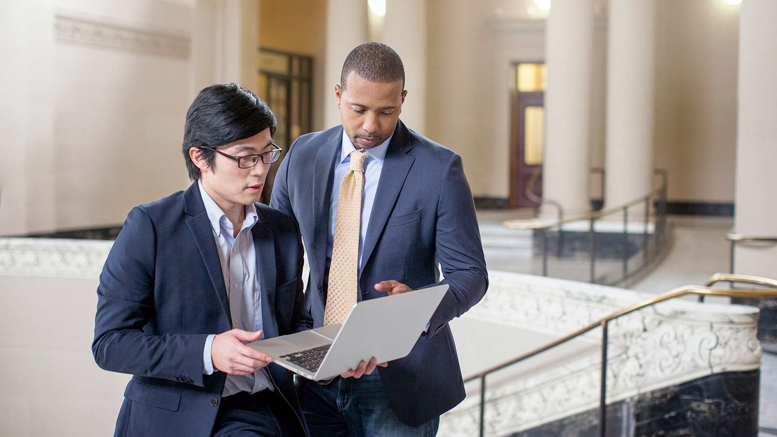 Two business men standing and conversing while looking at a laptop.