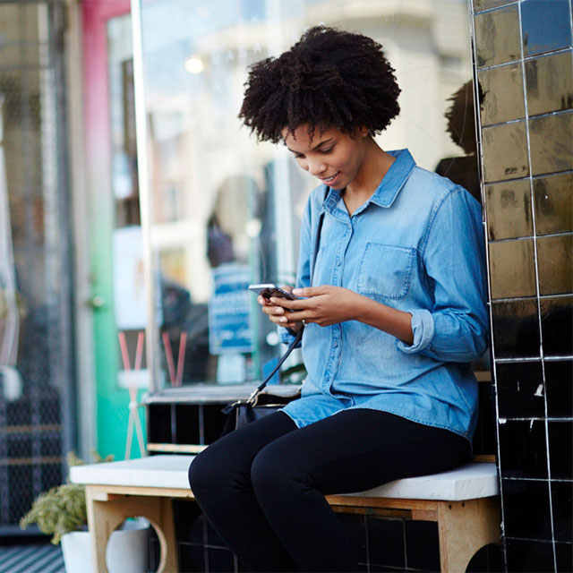 Woman smiling at phone on bench outside
