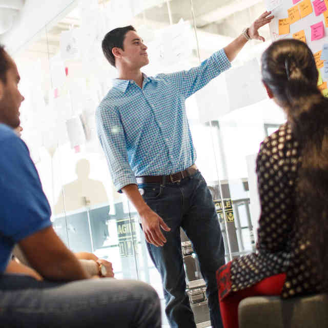 Man gesturing to a board with several post-it notes while two people look on.